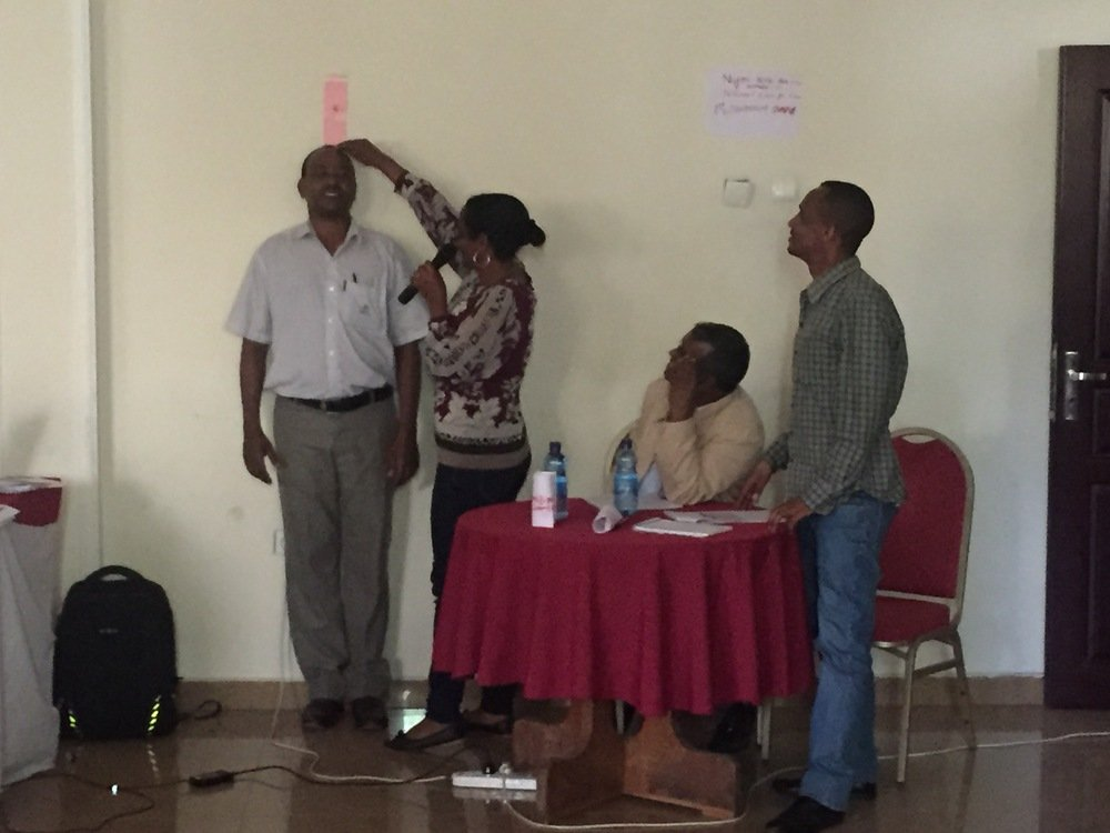 During the deworming day role play, regional health and education officials show how to use a dosing pole to determine the correct dose of praziquantel based on a child's height.
