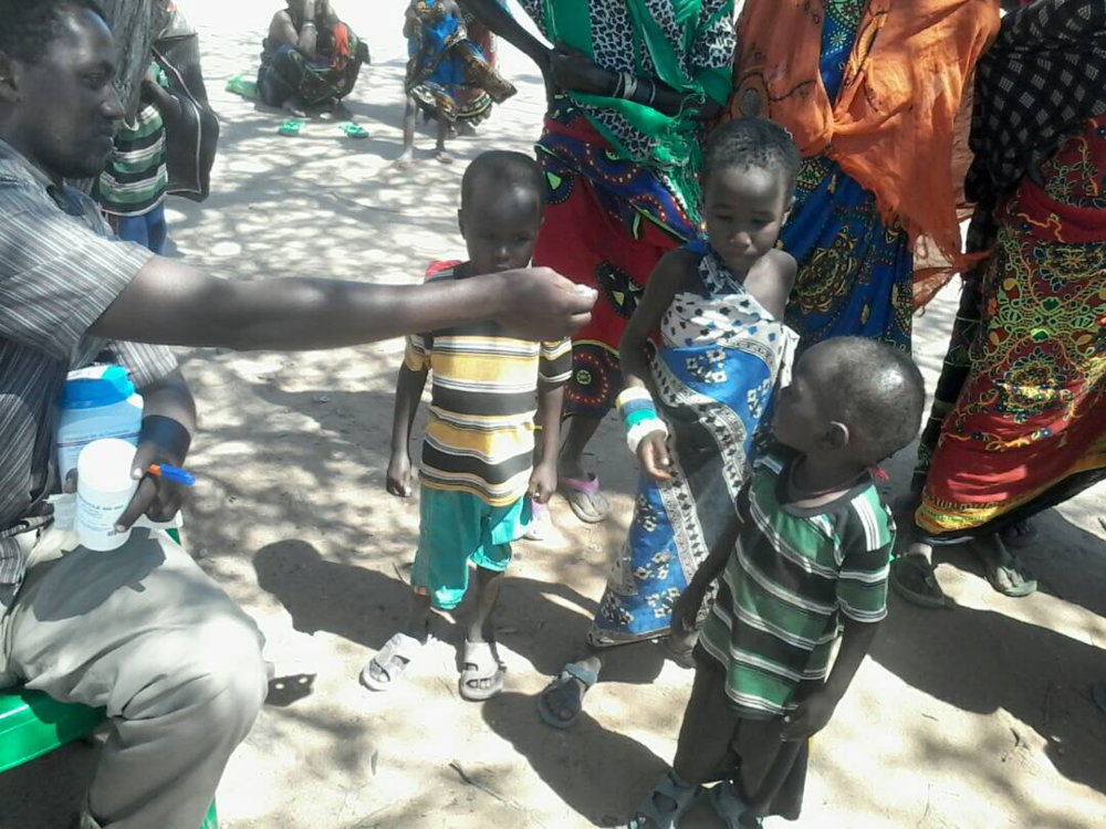 A teacher administers deworming tablets to children on deworming day in Tana River county.